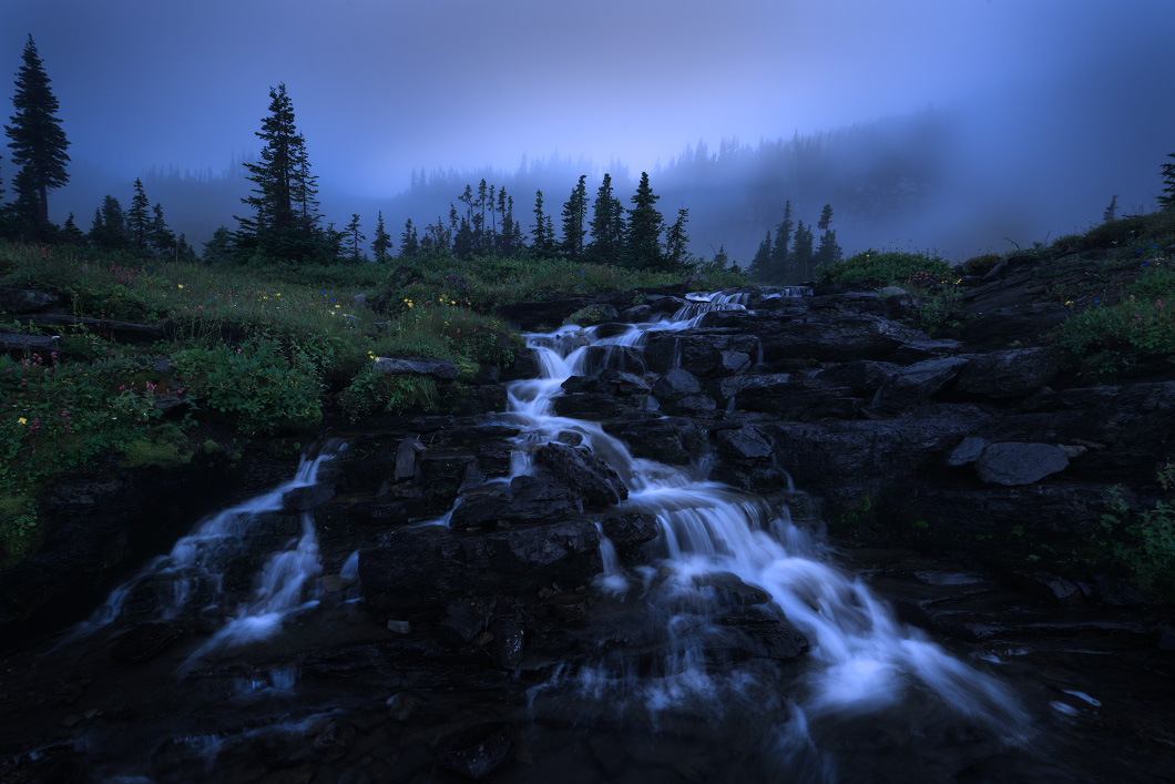 A fine art nature photograph of a foggy evening beside a waterfall at Glacier National Park, Montana by Bryce Mironuck