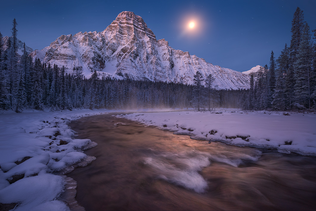 A fine art nature photograph taken at pre-dawn twilight, being lit by the moon at Mount Chephren in Alberta by Bryce Mironuck