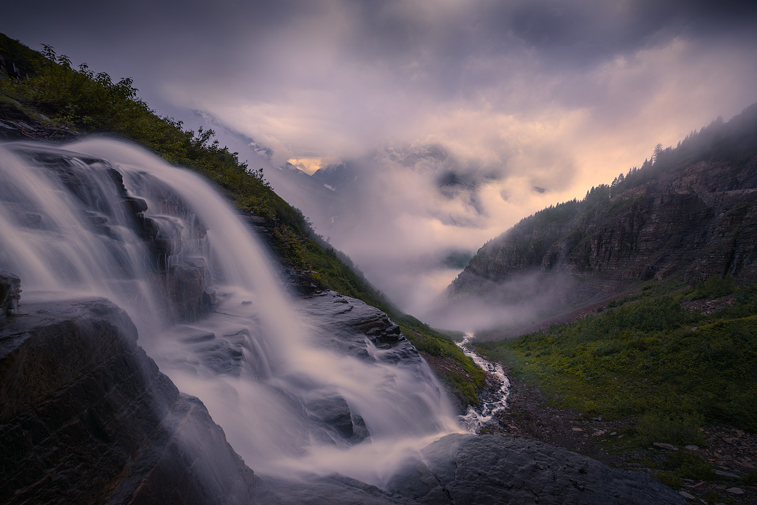 A fine art nature photograph of a waterfall, mountain, and fog in Glacier National Park, Montana, by Bryce Mironuck