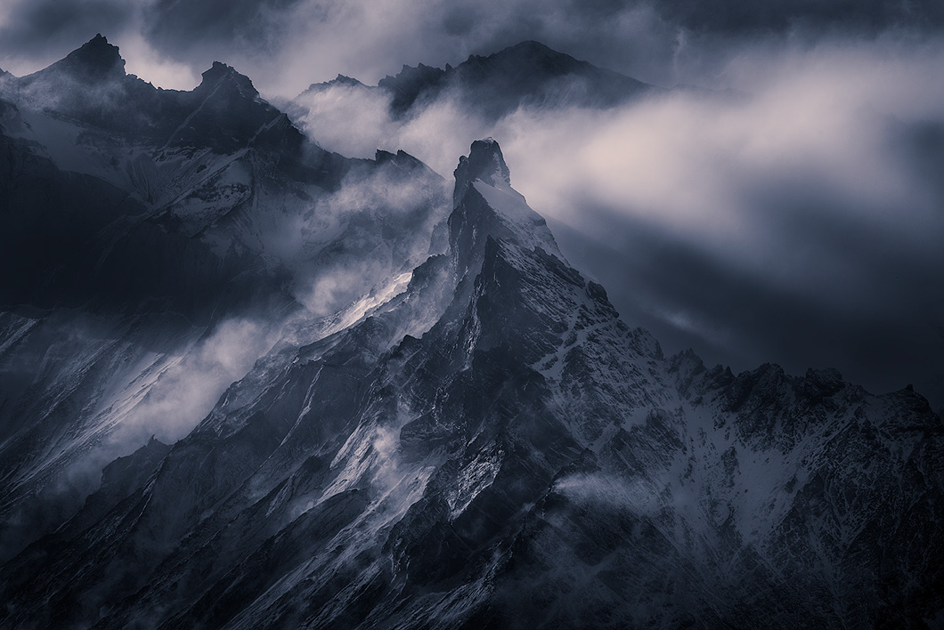A fine art nature photograph of a mountainous peak surrounded by cloud and light taken in Torres Del Paine, Chile by Bryce Mironuck