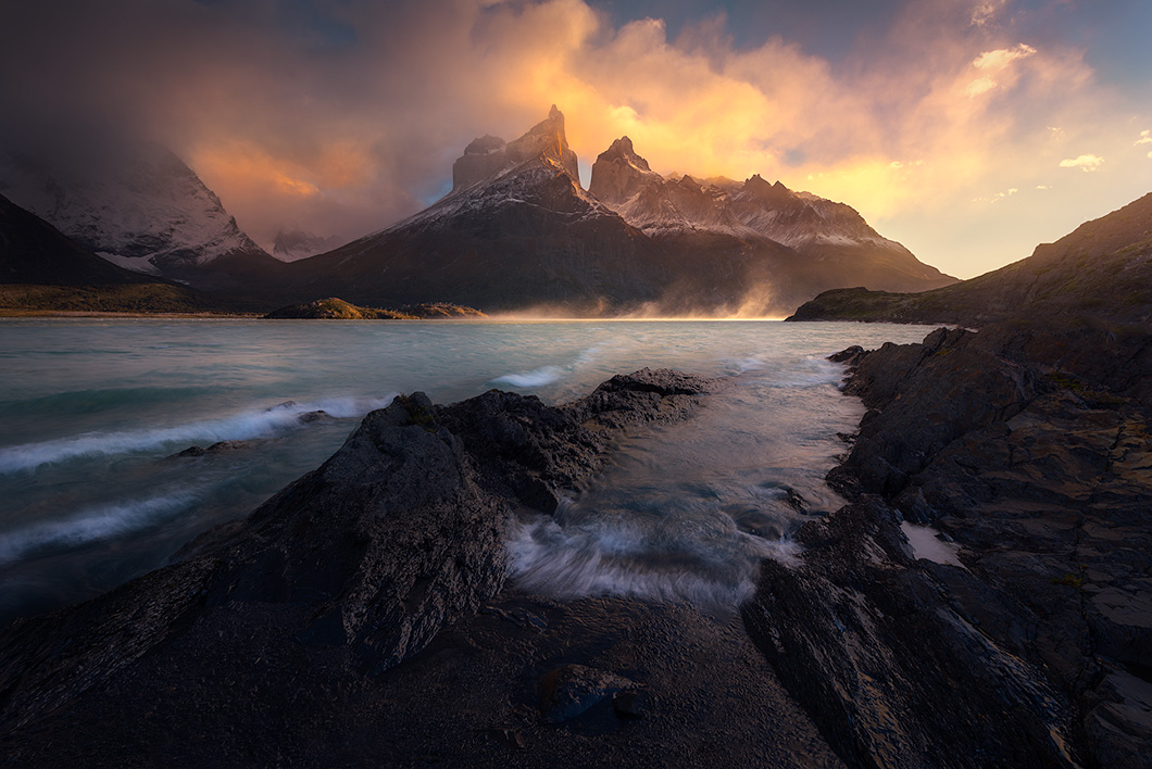 A fine art nature photograph taken at sunrise by a lake in Torres Del Paine with the Cuernos in the background by Bryce Mironuck