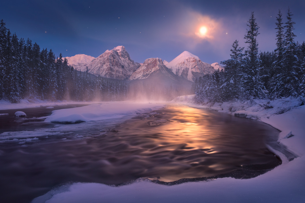 A fine art nature photograph taken in the moonlight illuminating the bow river along morants curve as mist rises off of the water in Alberta by Bryce Mironuck